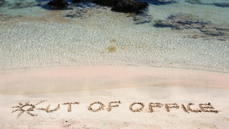 carved letters: OUT OF OFFICE written on sand on a beautiful beacOUT OF OFFICE written on sand on a beautiful beach, blue waves in background, blue waves in background .Relax concept image Stock Photo
