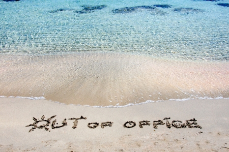 OUT OF OFFICE written on sand on a beautiful beacOUT OF OFFICE written on sand on a beautiful beach, blue waves in background, blue waves in background .Relax concept image Stock Photo