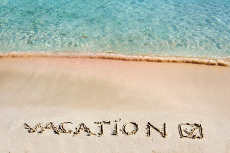 Vacation and checked mark written on sand on a beautiful beach, blue waves in background photo