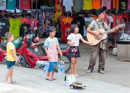 obtain:  Kanchanaburi, Thailand - May 23, 2014: Unidentified children sing and adult play guitar on the street to obtain money on May 23, 2014 in  Kanchanaburi, Thailand Editorial