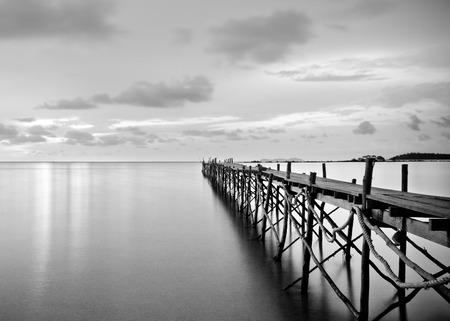 Fotografia preto e branco de um cais de madeira praia