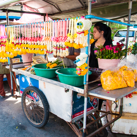 Maeklong, Thailand - May 24, 2014: Thai Street vendor of flower garlands in Maeklong, Thailand.Flower garlands are widely used in buddhist religious ceremonials and rituals.