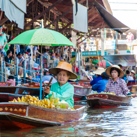 representations: Ratchaburi, Thailand - May 24, 2014: Thai locals sell food and souvenirs at famous Damnoen Saduak floating market on  May 24, 2014 in Thailand, in the old traditional way of selling from small boats.