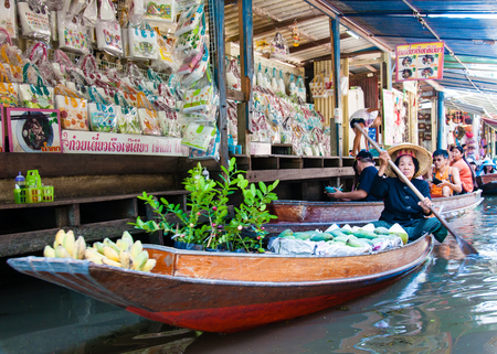 locals: Ratchaburi, Thailand - May 24, 2014: Thai locals sell food and souvenirs at famous Damnoen Saduak floating market on  May 24, 2014 in Thailand, in the old traditional way of selling from small boats.