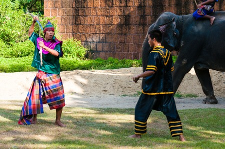 Nakhon Pathom, Thailand - May 24, 2014: Fighters exercise for\ Thai traditional martial demonstration at Samphran Elephant Ground\ & Zoo on May 24, 2014 in Nakhon Pathom,Thailand. Visitors can\ watch an elephant show complete with dramatic sounds and narrati
