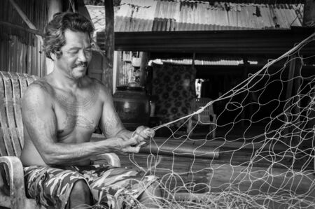 kood: Koh Kood Island, Thailand - June 1, 2014: Thai fishermen mending his fishing net at Baan AoYai Salad fishing village on Koh Kood Island, Thailand.Fishing is the main occupation and income source on the island Editorial