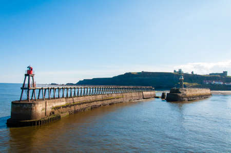 whitby: Scenic view of Whitby Pier in sunny autumn day.Whitby is a seaside town and port in North Yorkshire, UK.