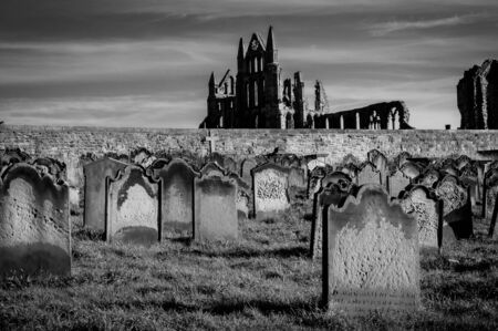 whitby: View of Whitby Abbey and cemetery during the night in North Yorkshire,UK.. Its attraction as a tourist destination is enhanced by its association with the world famous horror novel Dracula, written by Bram Stoker Editorial