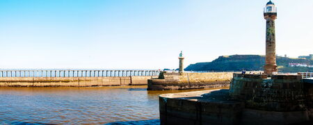 whitby: Whitby, North Yorkshire, UK - October 12, 2014: Scenic view of Whitby Lighthouse and Pier in sunny autumn day.Whitby is a seaside town and port in North Yorkshire, UK. Its attraction as a tourist destination is enhanced by its association with the world f
