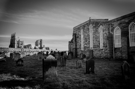 whitby: View of Whitby Abbey and cemetery during the night in North Yorkshire,UK.. Its attraction as a tourist destination is enhanced by its association with the world famous horror novel Dracula, written by Bram Stoker Stock Photo
