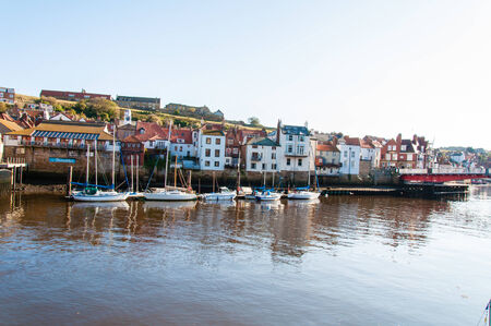 whitby: Whitby, North Yorkshire, UK - October 12, 2014: Scenic view of Whitby city and abbey in sunny autumn day.Whitby is a seaside town and port in North Yorkshire, UK. Its attraction as a tourist destination is enhanced by its association with the world famous