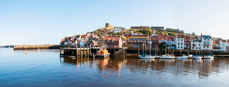 whitby: Scenic view of Whitby city and abbey in sunny autumn day.Whitby is a seaside town and port in North Yorkshire, UK. Its attraction as a tourist destination is enhanced by its association with the world famous horror novel Dracula, written by Bram Stoker