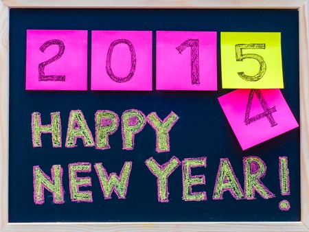 stated: Happy New Year 2015 message hand written on blackboard, numbers stated on post-it notes, 2015 replacing 2014, corporate office celebration concept