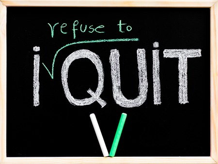 refuse: I refuse to quit message, handwriting with chalk on wooden frame blackboard, pieces on chalk in V shape, lifestyle change concept Stock Photo