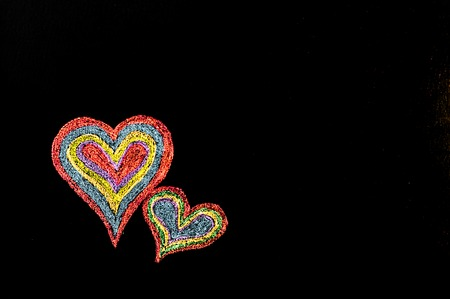 Conceptual image of love, with two vivid color shape hearts close one to each other .Vintage hand drawing on blackboard, isolated on black background, love concept, copy space available photo