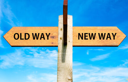 new way: Wooden signpost with two opposite arrows over clear blue sky, Old Way and New Way signs
