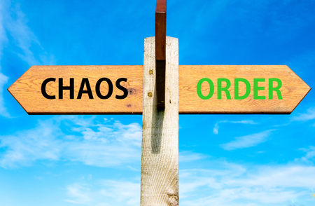chaos: Wooden signpost with two opposite arrows over clear blue sky, Chaos versus Order messages