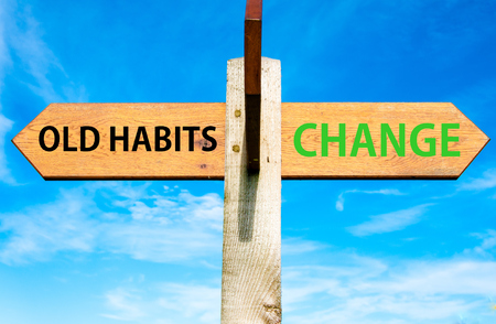 Placa de madeira com duas setas opostas sobre o céu azul claro, velhos hábitos versus mensagens de mudança, estilo de vida mudar imagem conceitual