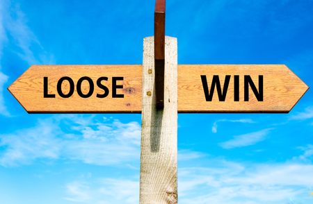 Wooden signpost with two opposite arrows over clear blue sky, Loose versus Win messages, Lifestyle change conceptual image photo