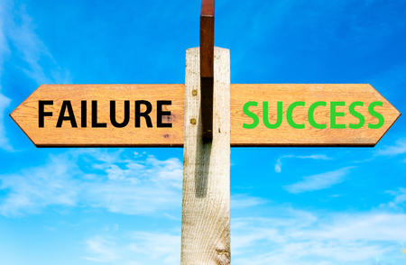 opting: Wooden signpost with two opposite arrows over clear blue sky, Failure and Success messages, Success conceptual image