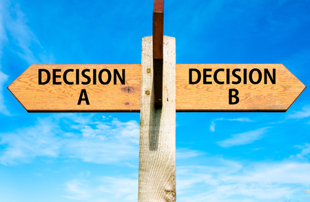 Wooden signpost with two opposite arrows over clear blue sky, Decision A and Decision B messages, Right choice conceptual image photo