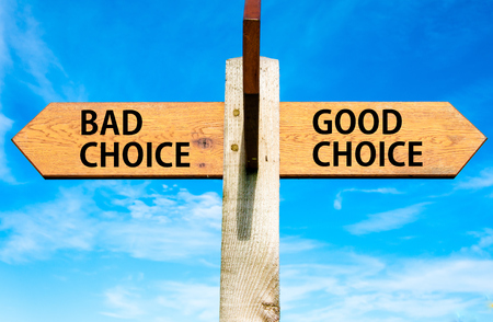 bad planning: Wooden signpost with two opposite arrows over clear blue sky, Bad Choice and Good Choice messages, Right choice conceptual image Stock Photo