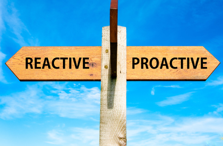 Wooden signpost with two opposite arrows over clear blue sky, Reactive versus Proactive messages, Behaviour conceptual image