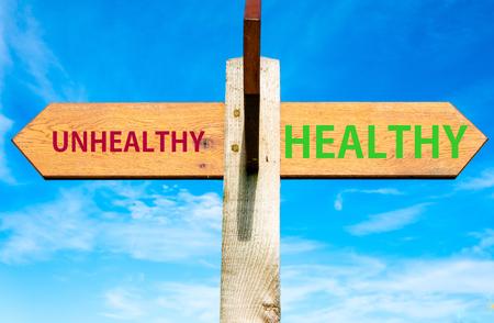 澄んだ青い空、不健康なメッセージ、健康的なライフ スタイル イメージと健康上 2 つの反対の矢印と木製の道標