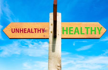 Wooden signpost with two opposite arrows over clear blue sky, Healthy versus Unhealthy messages, Healthy Lifestyle conceptual image