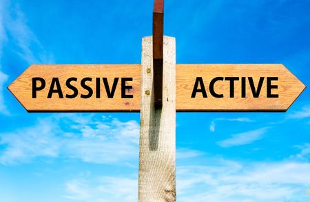Houten bord met twee tegenovergestelde pijlen over de heldere blauwe hemel, Passief versus Actief berichten, Lifestyle verandering conceptueel beeld Stockfoto
