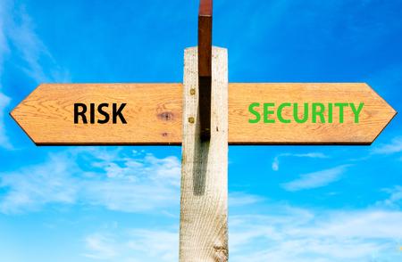 澄んだ青い空に 2 つの反対の矢印と木製の道標、リスク セキュリティ メッセージ、ライフ スタイルとは概念のイメージを変更します。 写真素材