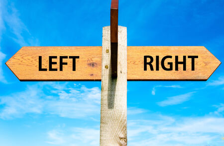clear path: Wooden signpost with two opposite arrows over clear blue sky, Left versus Right messages, Choice conceptual image