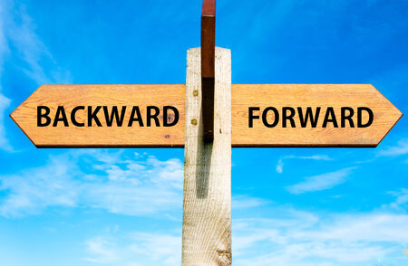 back and forth: Wooden signpost with two opposite arrows over clear blue sky, Backward versus Forward messages Stock Photo