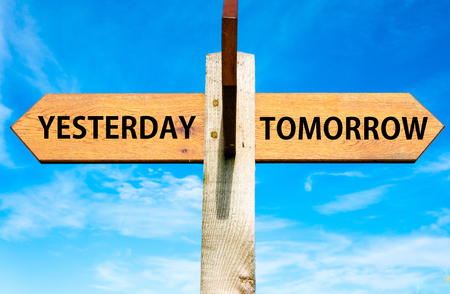 yesterday: Wooden signpost with two opposite arrows over clear blue sky, Yesterday versus Tomorrow messages Stock Photo