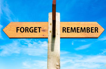 澄んだ青い空、忘れて覚えているメッセージに対する 2 つの反対の矢印と木製の道標 写真素材