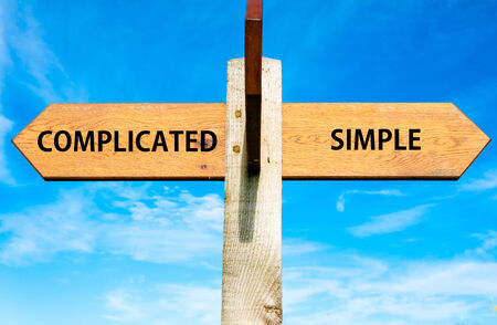 Wooden signpost with two opposite arrows over clear blue sky, Complicated versus Simple messages Stock Photo