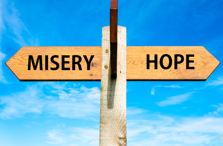 Wooden signpost with two opposite arrows over clear blue sky, Misery versus Hope messages