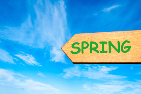 spring message: Wood arrow sign against clear blue sky with Spring message, Season change conceptual image