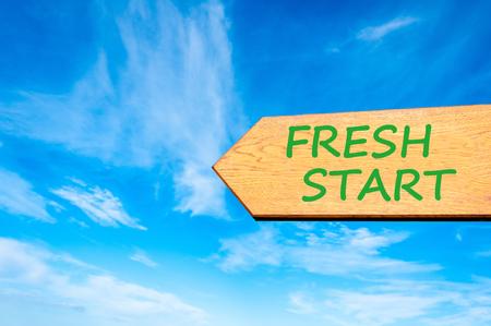 frisse start: Houten pijl tekenen tegen de heldere blauwe hemel met Fresh Start, Life veranderen conceptueel beeld