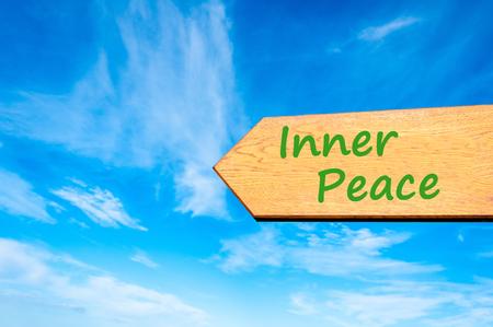 Holzpfeil Zeichen gegen den blauen Himmel mit Inner Peace Nachricht Standard-Bild