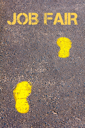 Yellow footsteps on sidewalk towards Job Fair message, Career change conceptual image Stock Photo