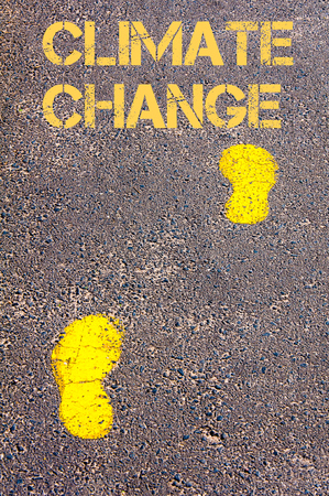 change direction: Yellow footsteps on sidewalk towards Climate Change message.Conceptual image