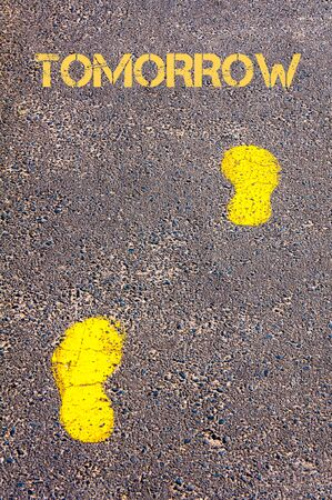 Yellow footsteps on sidewalk towards Tomorrow message, Time conceptual image
