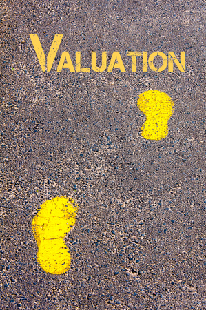 valuation: Yellow footsteps on sidewalk towards Valuation message.Conceptual image