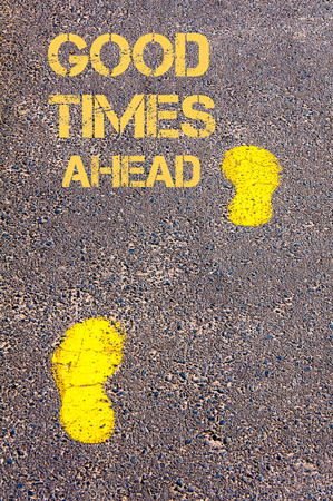 good times: Yellow footsteps on sidewalk towards Good Times Ahead message.Conceptual image
