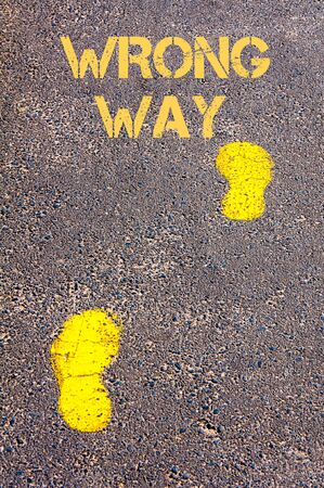 wrong way: Yellow footsteps on sidewalk towards Wrong Way message.Conceptual image