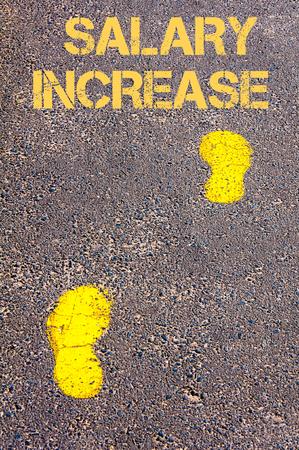 remuneraci�n: Huellas amarillas en acera imagen message.Conceptual aumento salarial hacia