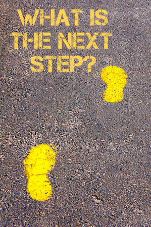 Yellow footsteps on sidewalk towards What is the next step message.Conceptual image Stock Photo
