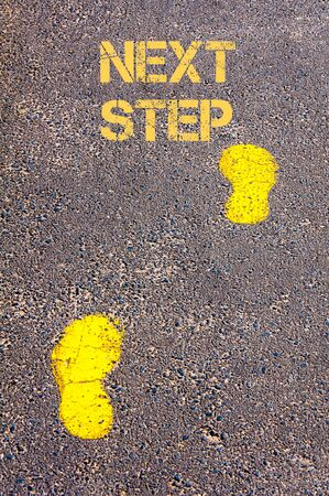 Yellow footsteps on sidewalk towards Next Step message.Conceptual image Stock Photo