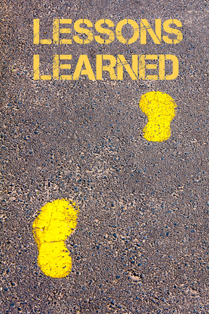 learned: Yellow footsteps on sidewalk towards Lessons Learned message.Conceptual image Stock Photo